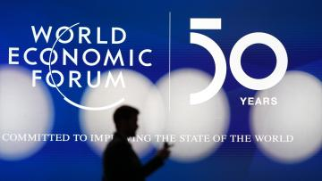 A man silhouettes in front of the logo of the World Economic Forum in Davos, Switzerland