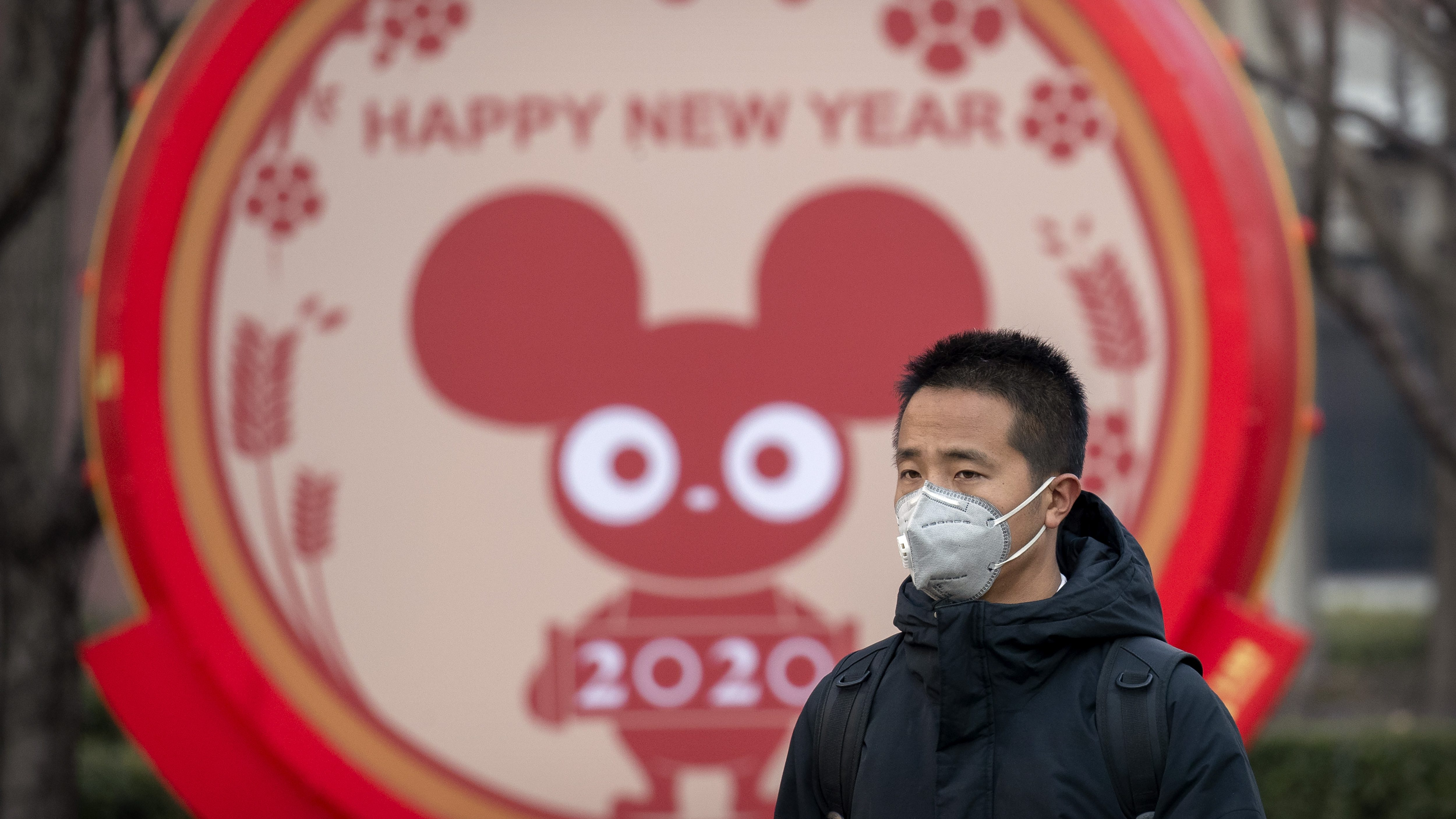 A man wears a face mask as he walks past a display for the upcoming Lunar New Year, the Year of the Rat, in Beijing, Wednesday, Jan. 22, 2020.