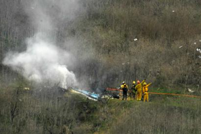 Firefighters work at the scene of the crash where former NBA star Kobe Bryant died.