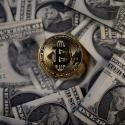 A gold token representing a bitcoin floats above a pile of US dollars.