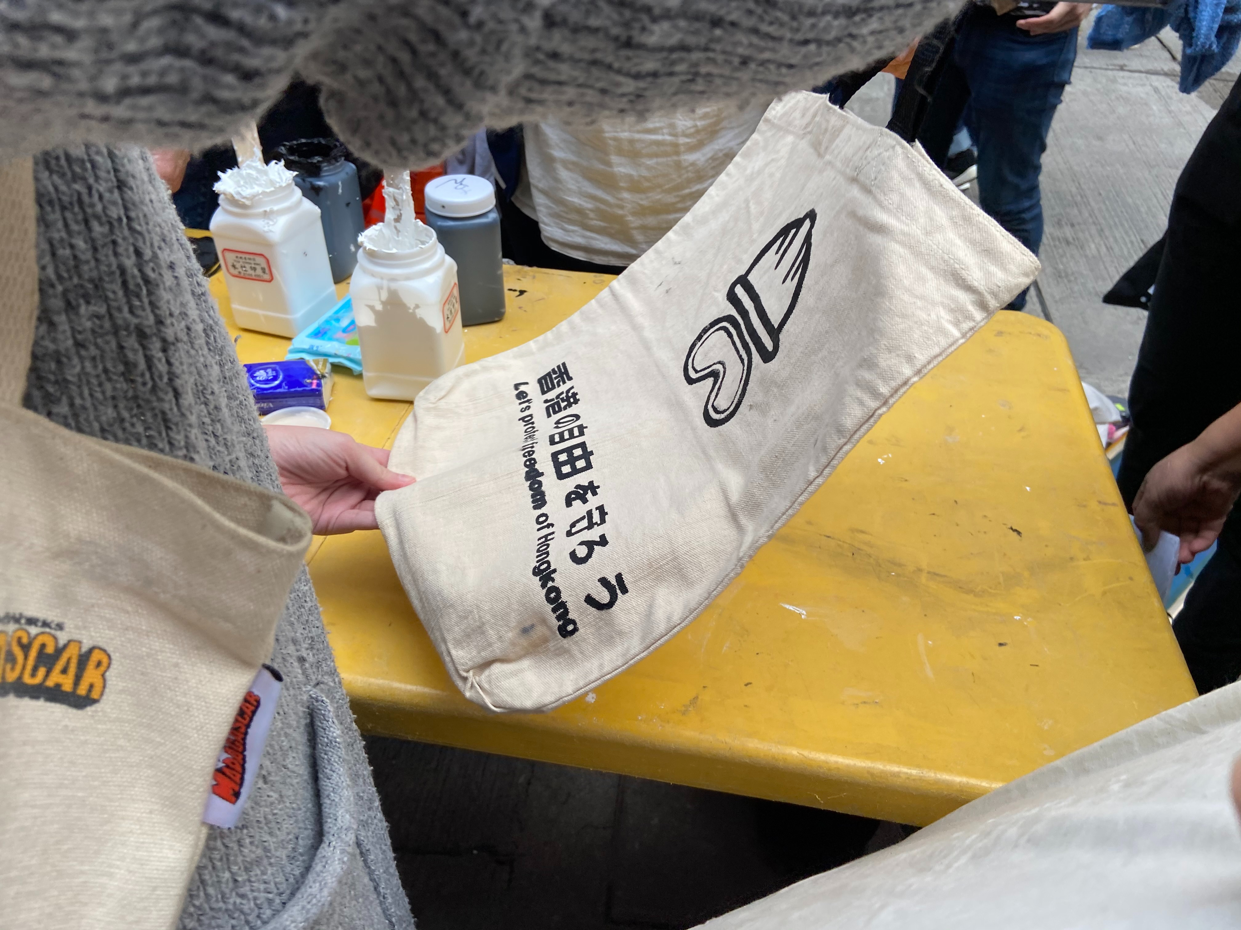 A woman gets her bag stamped with a protest logo and slogan at an alternative Lunar New Year market in Sai Ying Pun, Hong Kong, Jan. 19, 2020.
