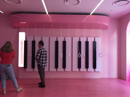 Museum of Ice Cream visitors stand in front of a giant piano