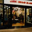 Shoppers walk by a Lucky Brand Jeans shop.