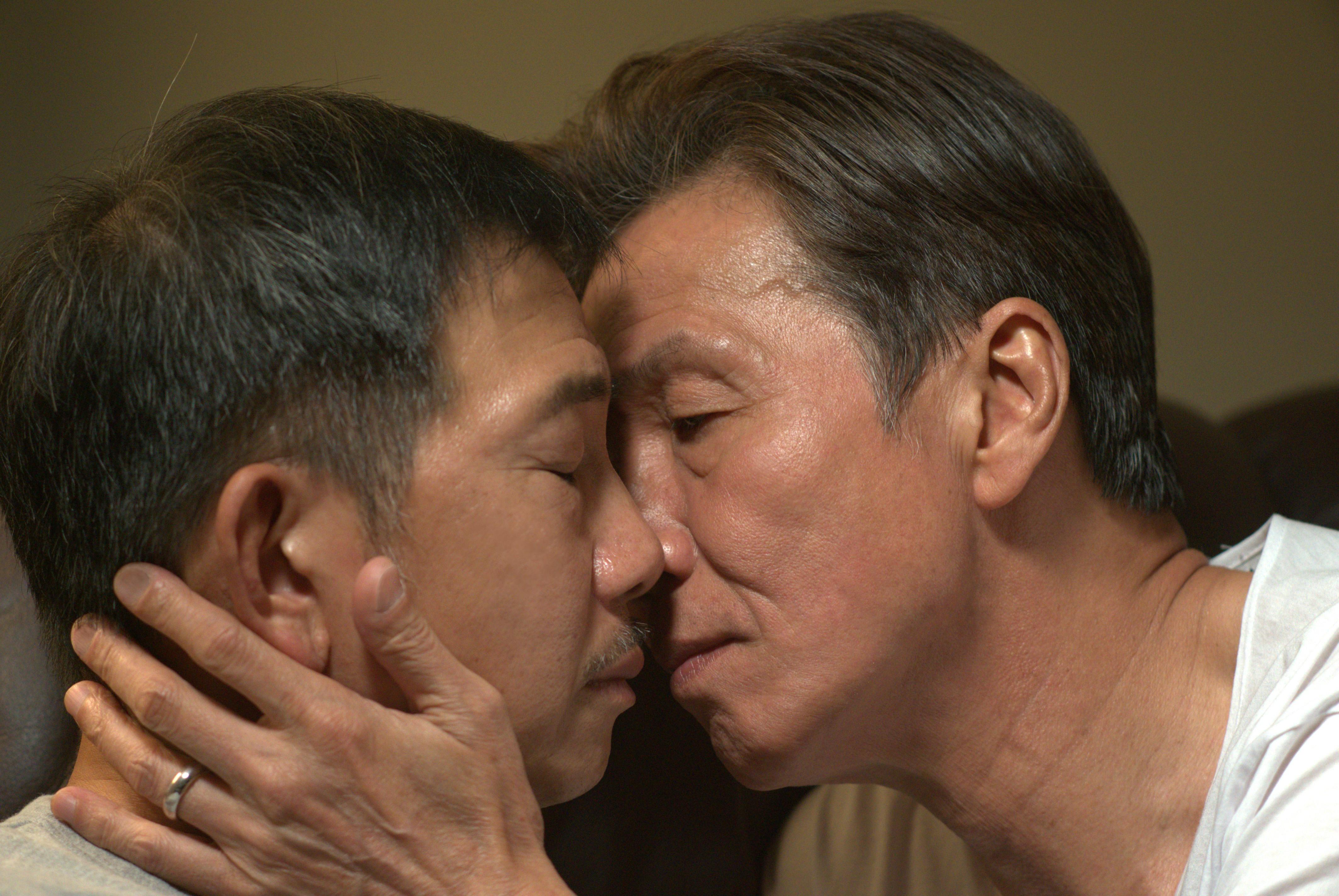"Forbidden love: elderly gay lovers Hoi (left) and Pak share an intimate moment in secret in 'Suk Suk""."