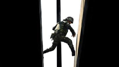 A person in camouflage jumps from one roof top to another.
