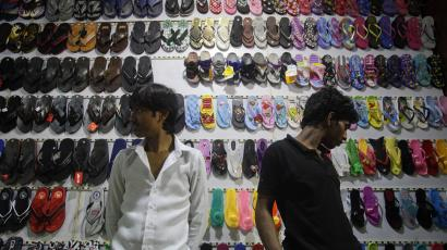Shop attendants wait for customers at a shoe shop in Mumbai