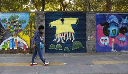 "Commuters walk past graffiti themed ""Design the Change"" on a wall of the University of Delhi campus"