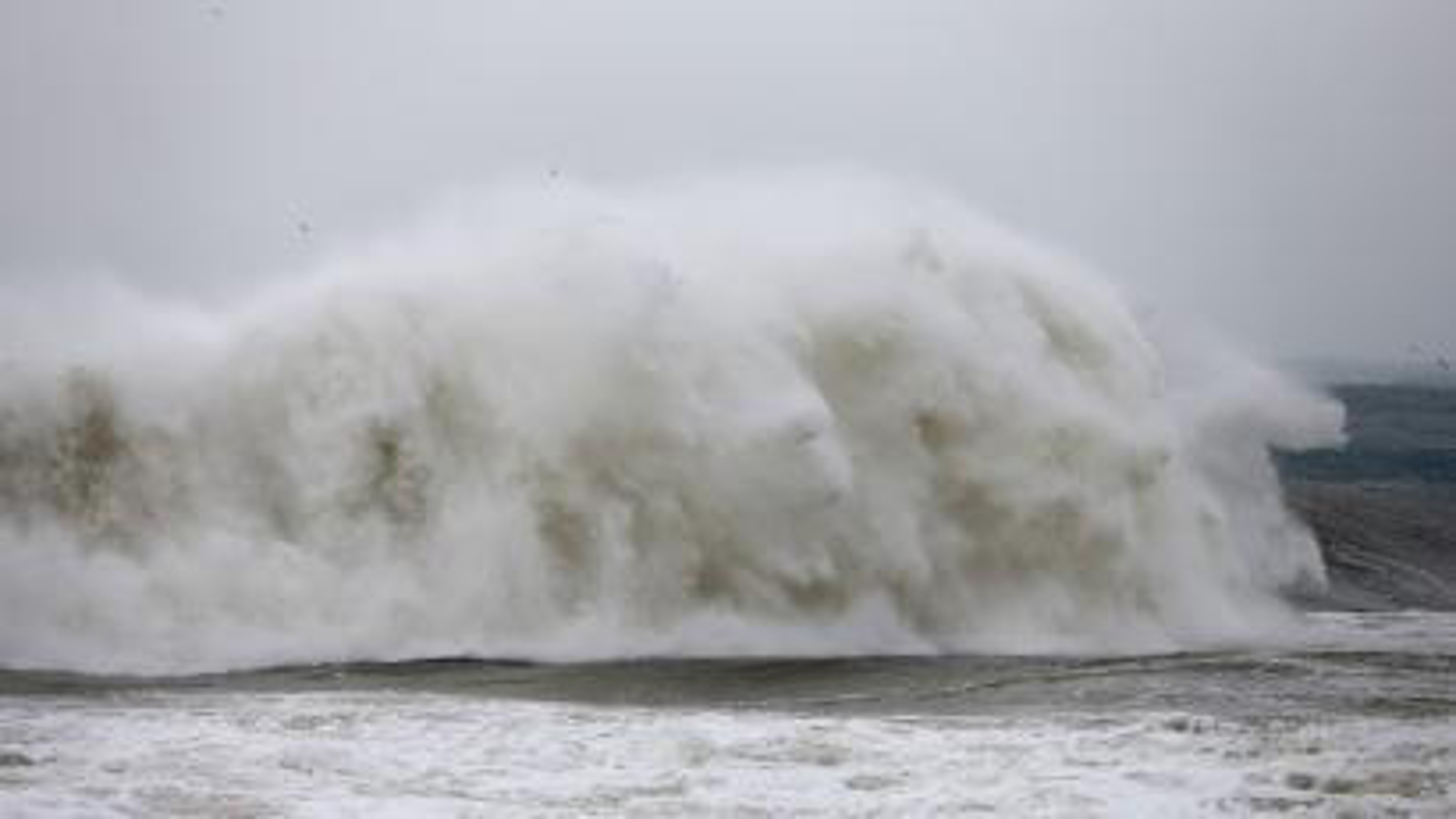 A big wave breaking on a shoreline