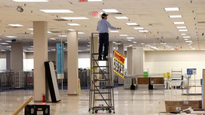 A worker removes sale banners inside a closed Sears department store
