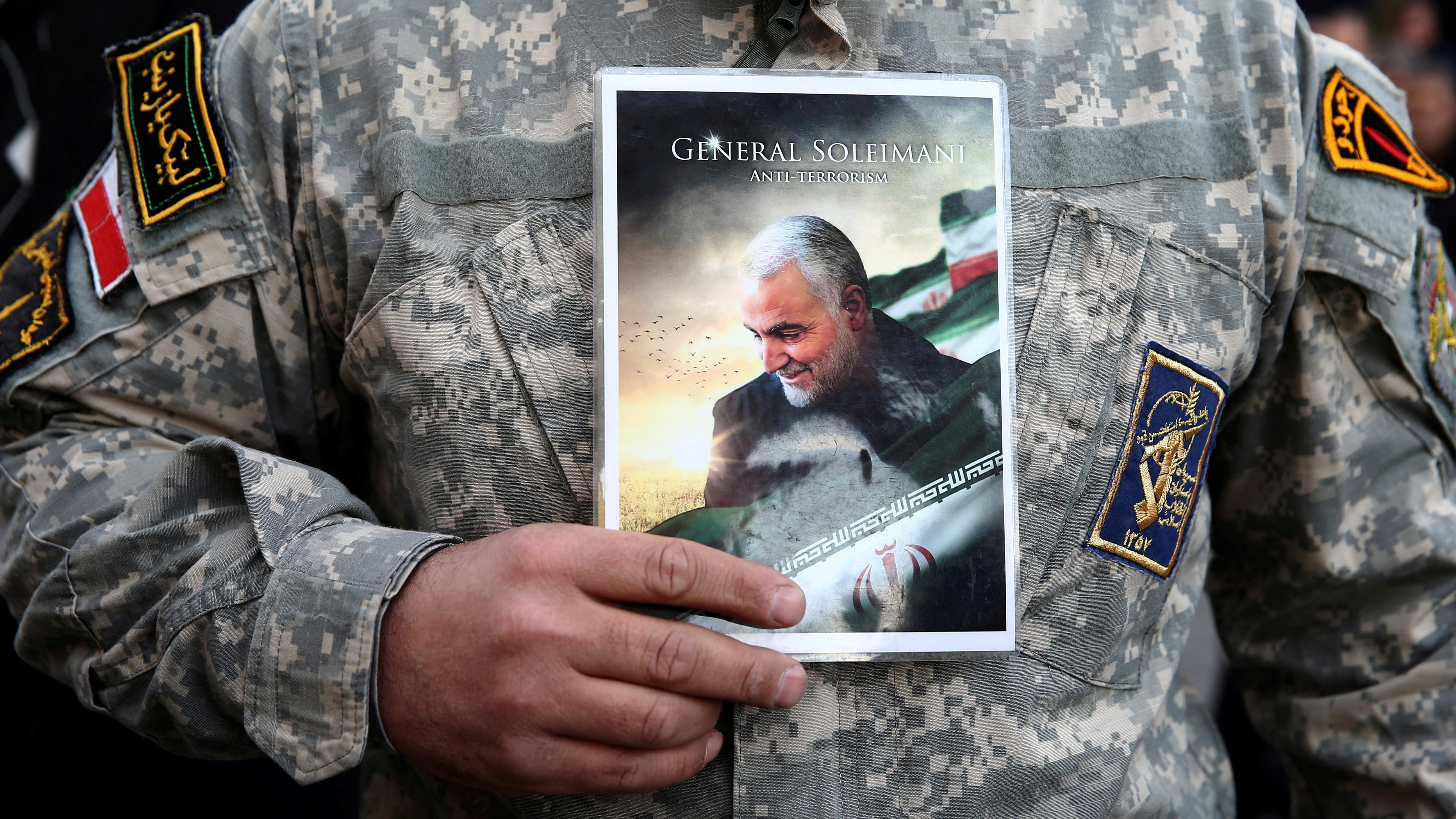 A demonstrator in Tehran holds a picture of Qassem Soleimani during a protest against the US assassination of the Iranian major general.