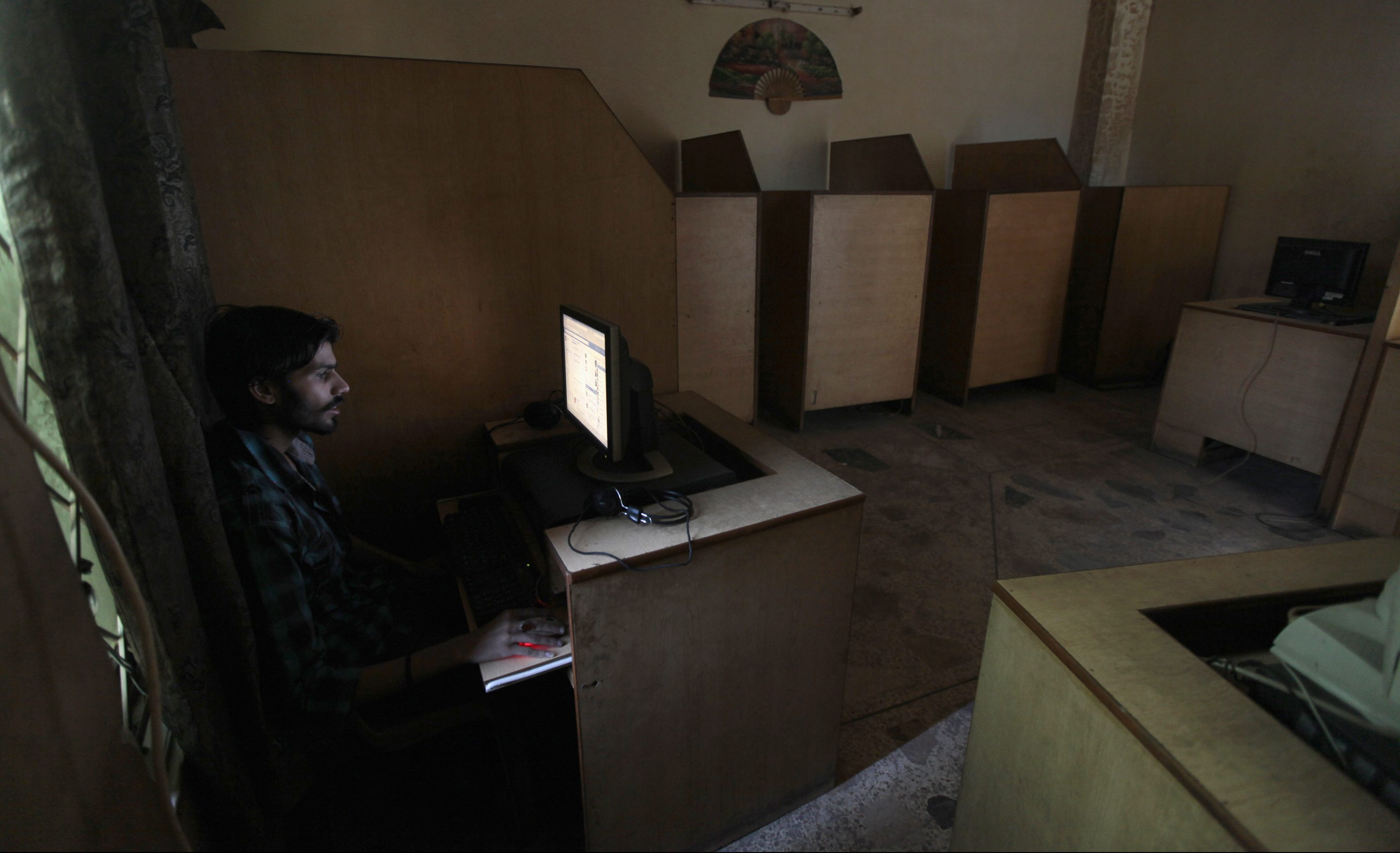A man uses the computer at an internet cafe in Rawalpindi