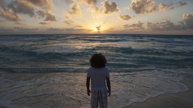A man faces the sun rising over ocean waves.