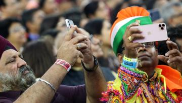 "People take photos with their mobile phones as they participate in the ""Howdy Modi"" event in Houston"