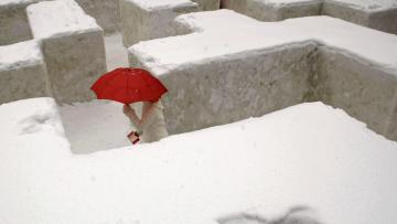 A woman with a red umbrella travels through a snowy