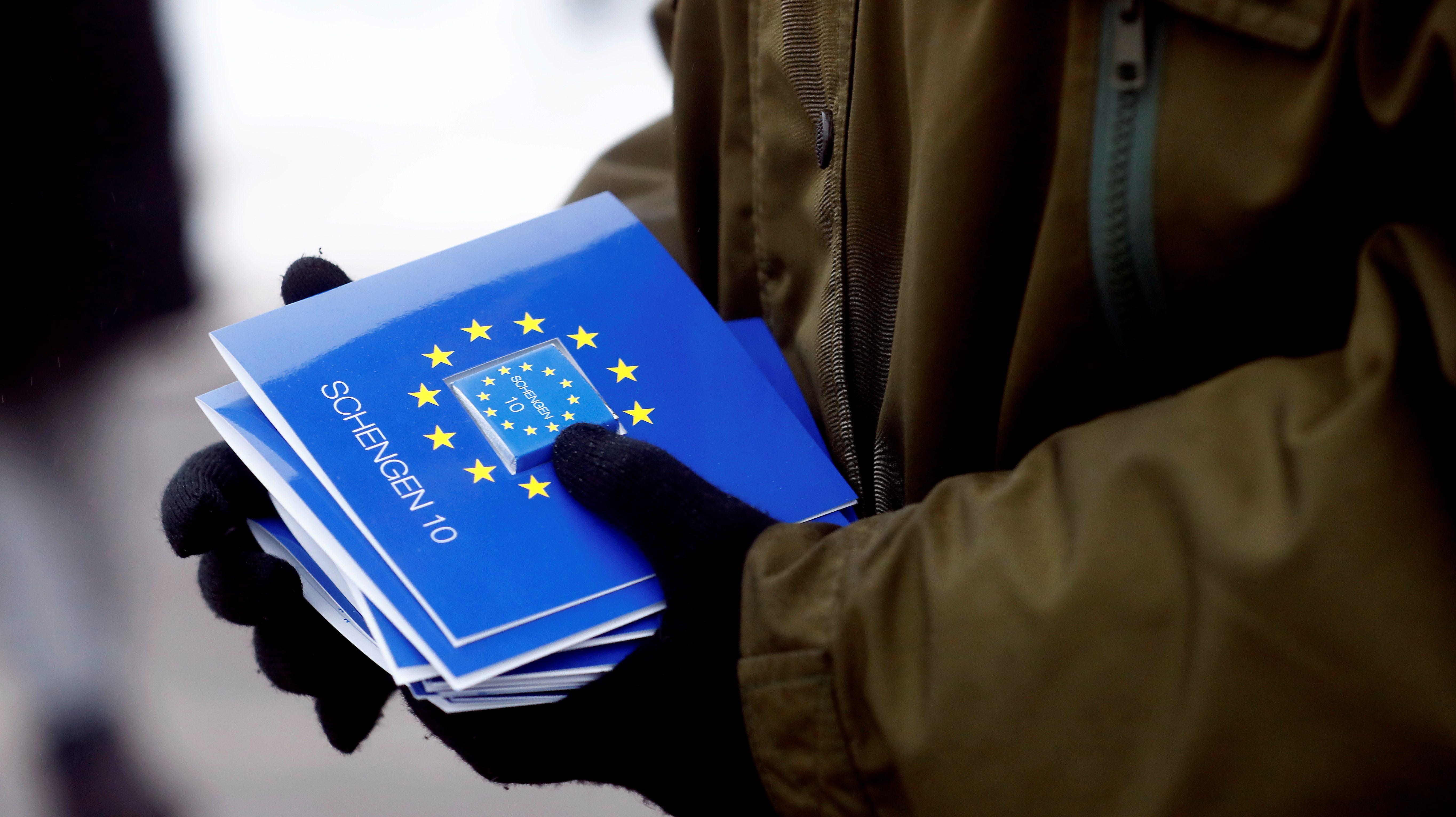 """An Estonian border guard holds booklets marked """"Schengen."""""""