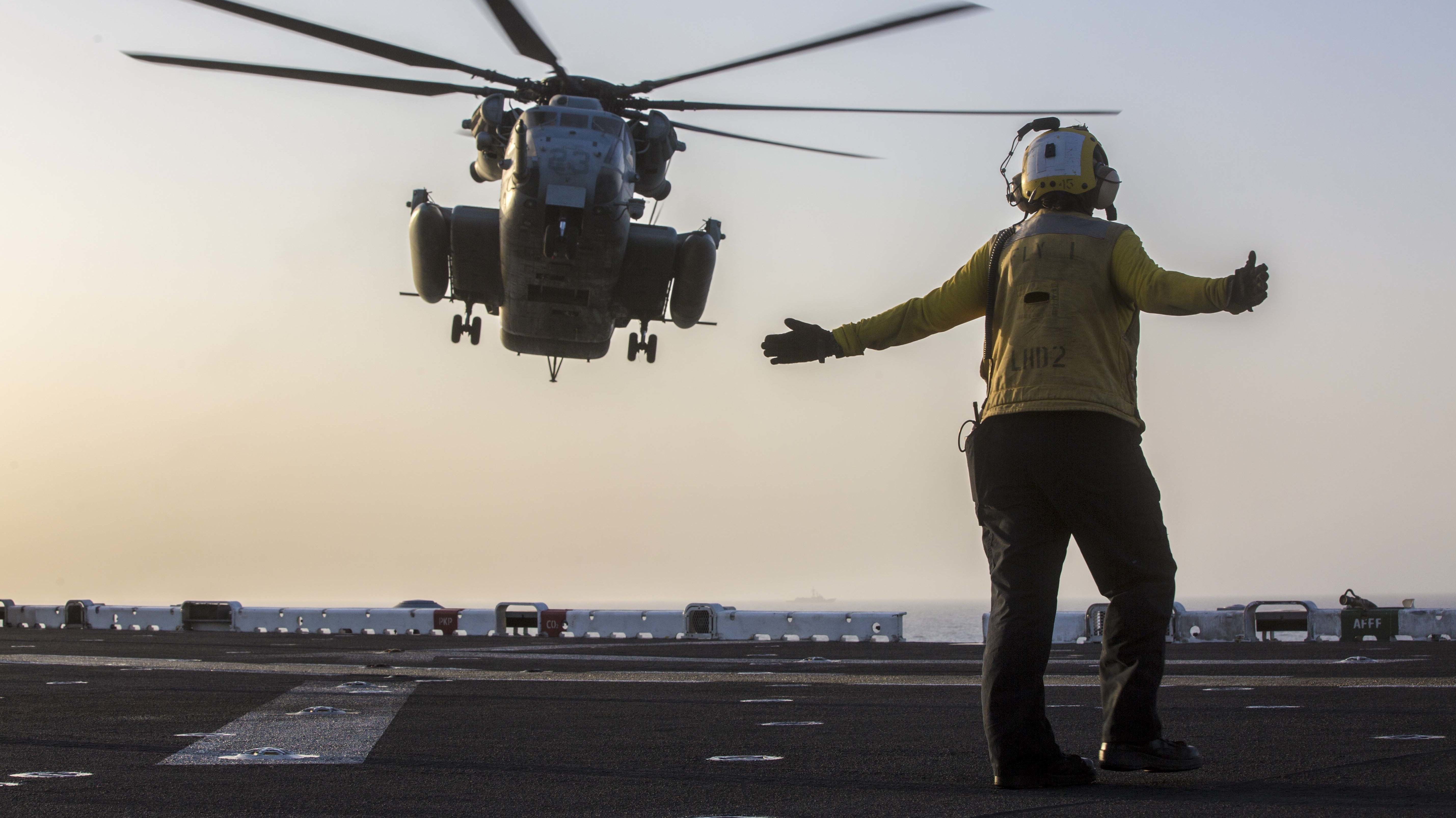 A helicopter lands on the USS Essex