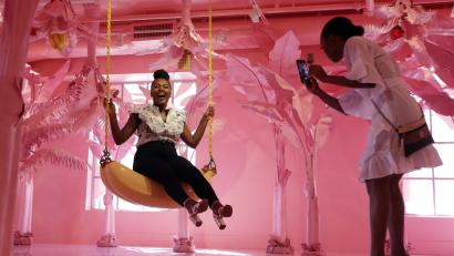 A woman sits on a banana swing while her friend takes a photo at the Museum of Ice Cream