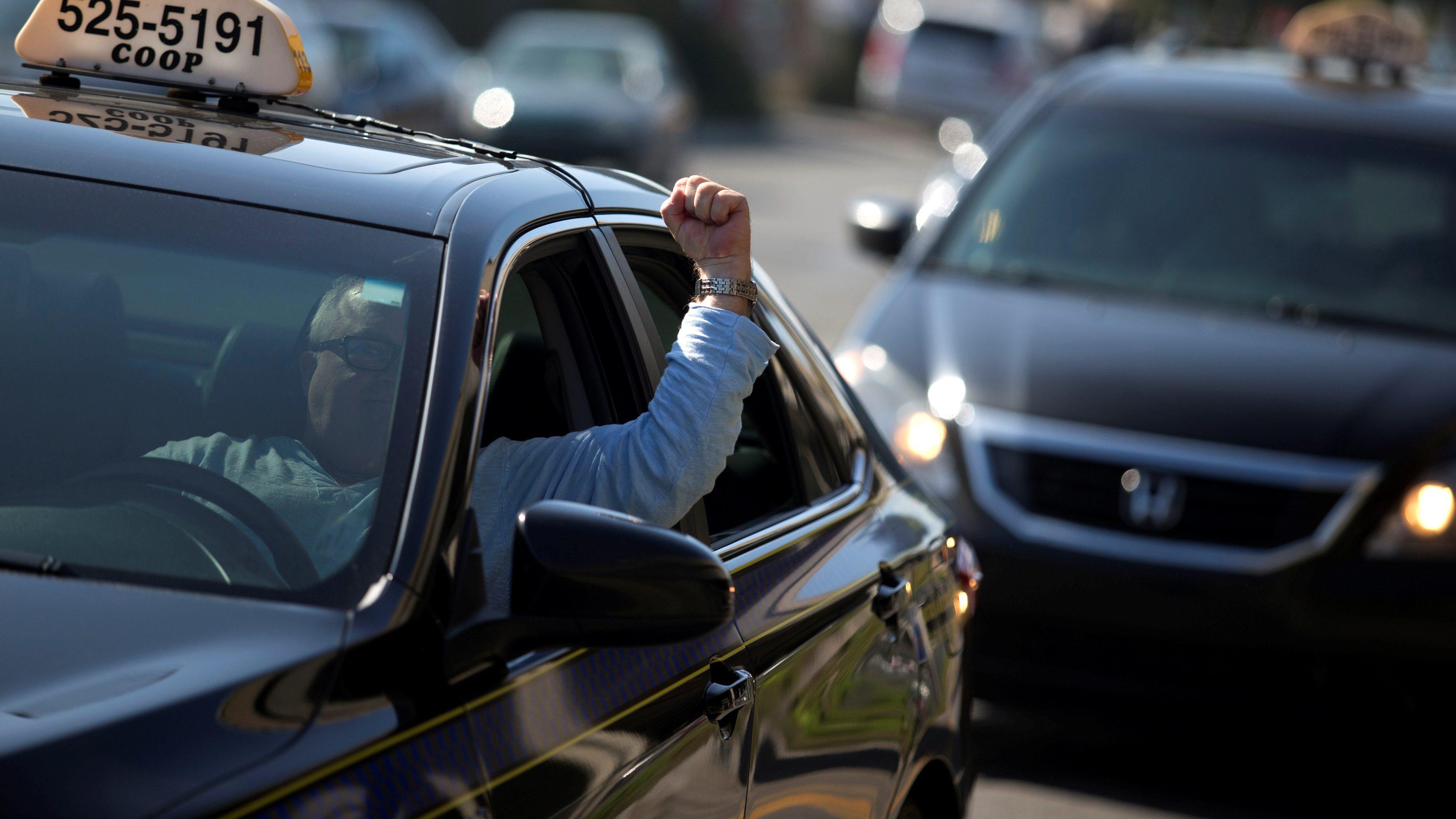 A taxi driver raises his fist through the car window.