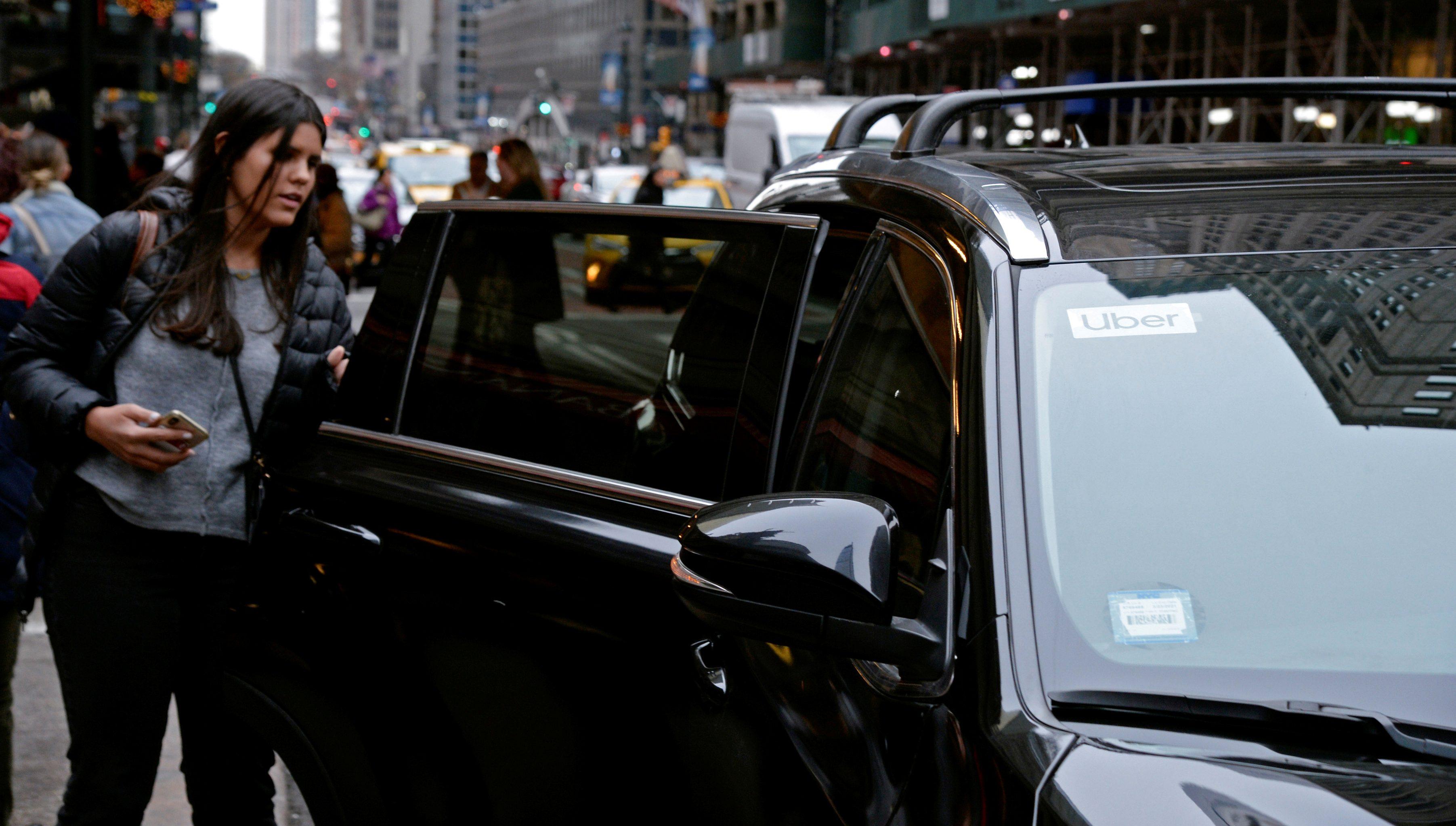 A passenger gets into an Uber car