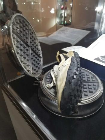A pair of Nike shoes from 1972 with the waffle tread sole, sitting atop a waffle iron
