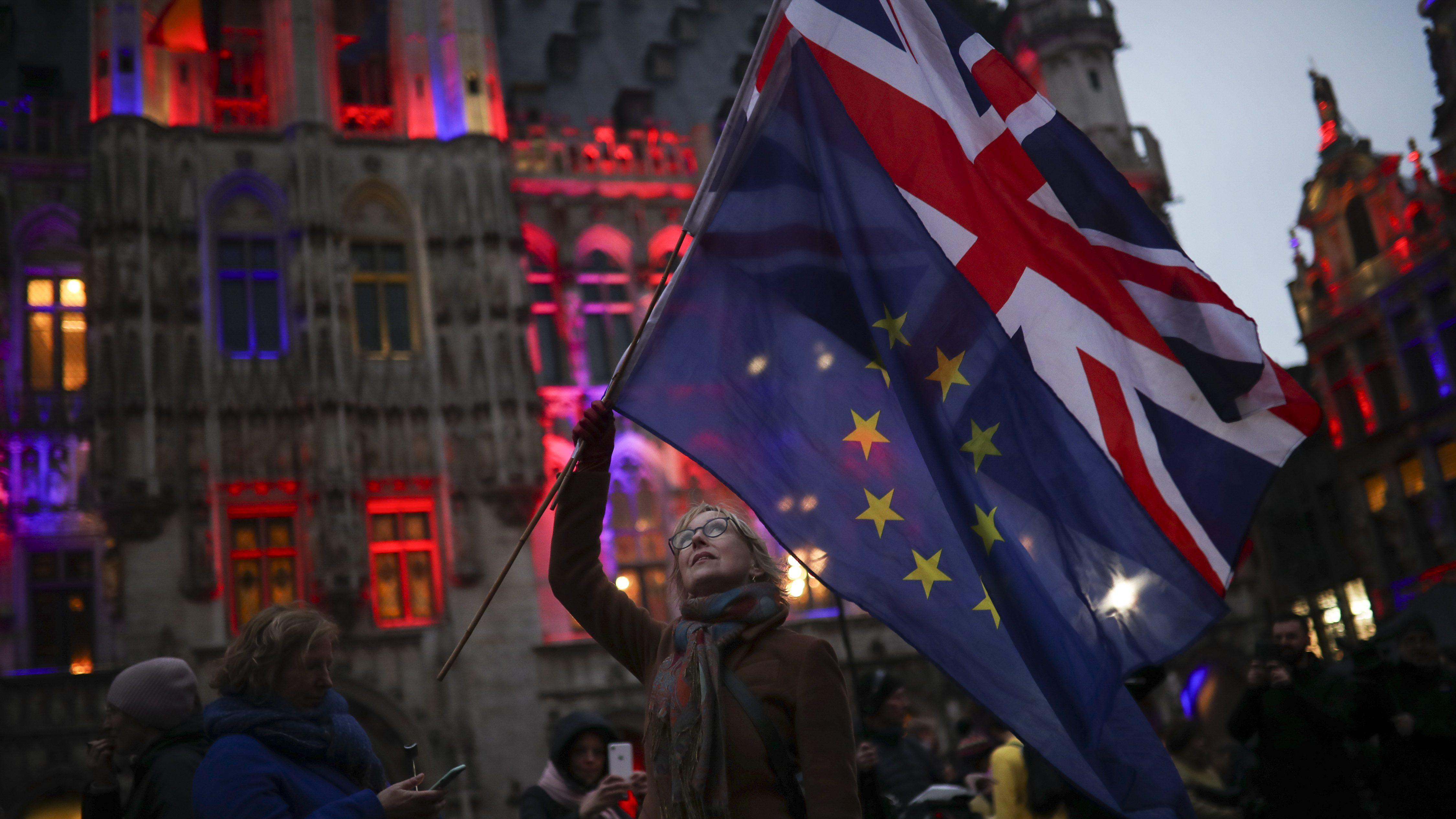 Uma mulher segura as bandeiras da União e da União Europeia durante um evento chamado