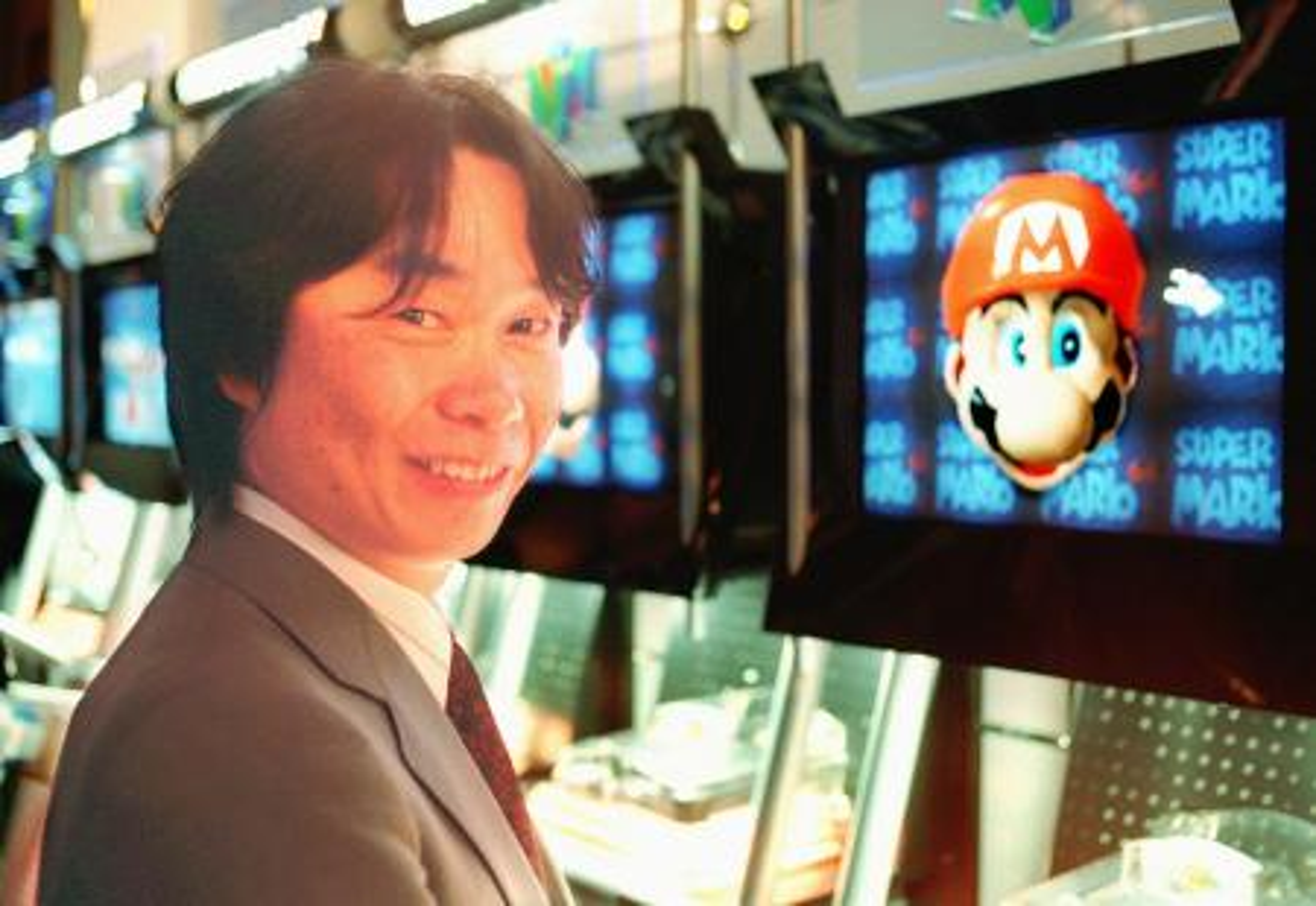 Shigeru Miyamoto in front of a screen displaying with his creation, Mario