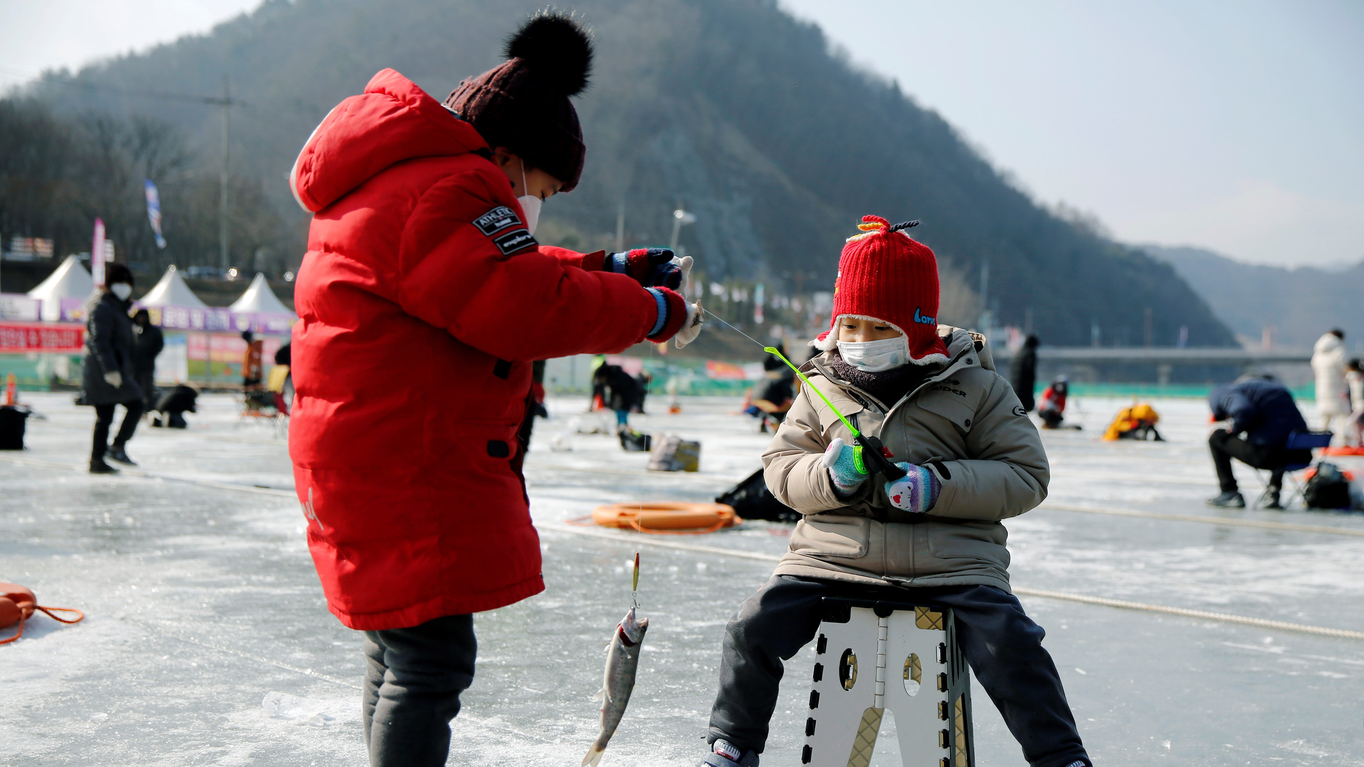 Children wearing masks to prevent contacting a new coronavirus look on a trout on a frozen river