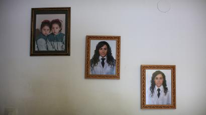 Photographs of two young Spanish nurses hang on the wall of their home