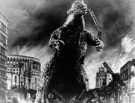 Radioactive monster Godzilla stomps through a city and eats a commuter train in a scene from 'Godzilla, King of the Monsters!,' directed by Ishiro Honda and Terry O. Morse, 1956