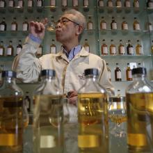 """In this March 8, 2017 photo, Suntory's chief blender Shinji Fukuyo demonstrates how he examines the whisky at the Suntory distillery in Yamazaki, near Kyoto, western Japan. """"What's important for whisky is that its deliciousness must deepen with aging, sitting in the casks for a long time,"""" said Fukuyo, 55, demonstrating how he examines the whisky in a glass, swirling the crystalline amber spirit against the light."""