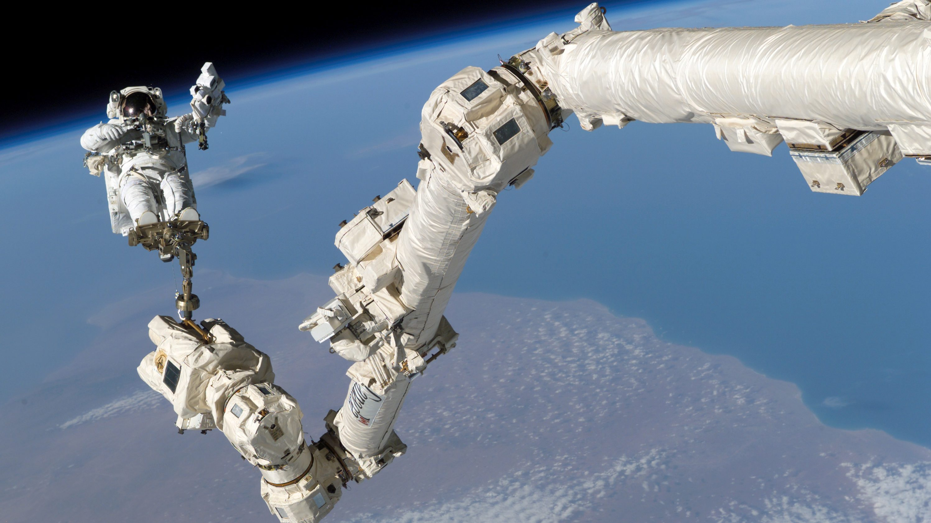 NASA astronaut Stephen K. Robinson is anchored to a foot restraint on the International Space StationÕs Canadarm2, built by Canadian technology company MDA, during his Space Shuttle missionÕs third session of extravehicular activity (EVA) August 3, 2005.