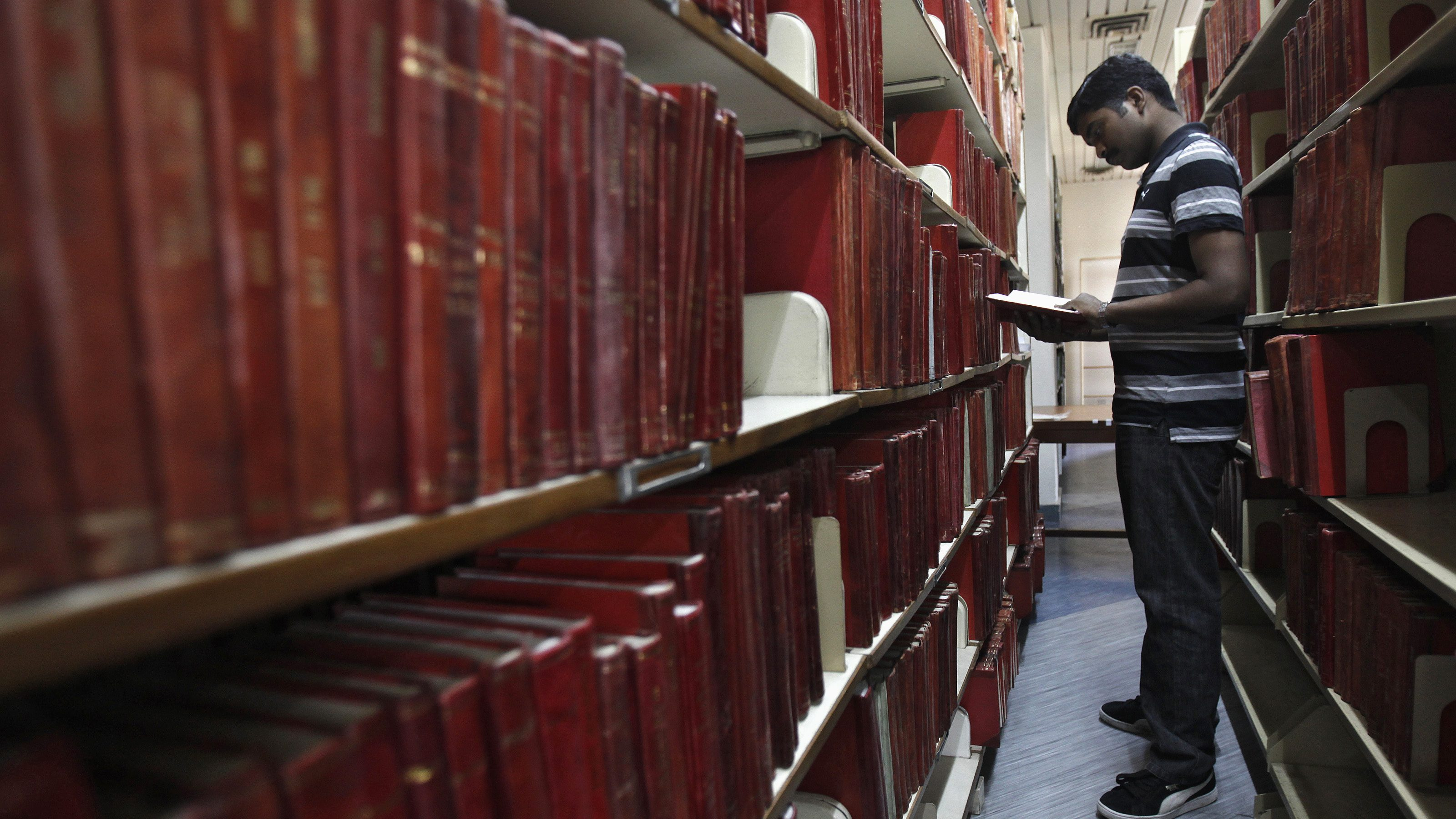 Master of Business Administration student looks for book in library at Management Development Institute in Gurgaon