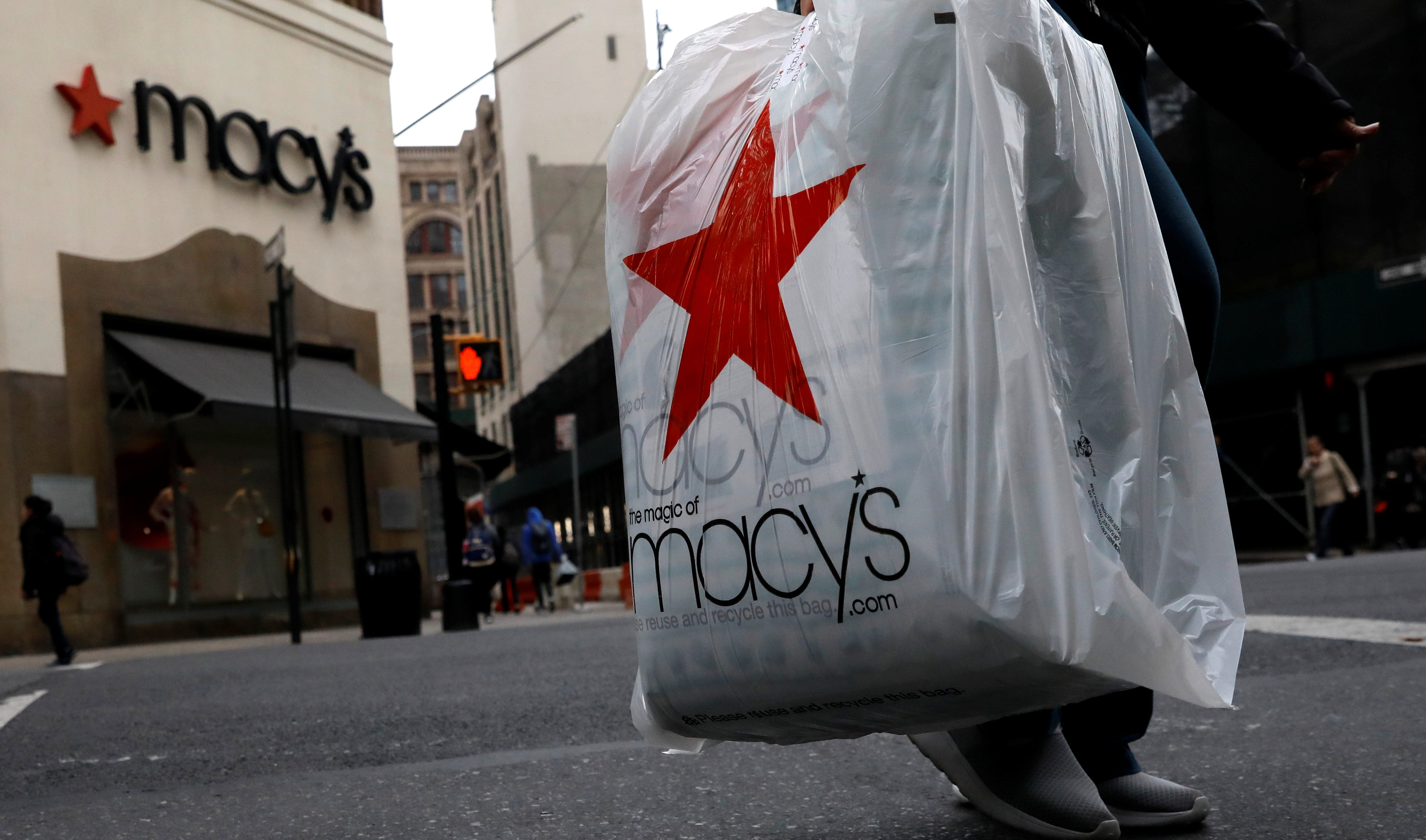 A customer carries a Macy's bag after exiting a Macy's store