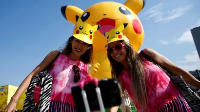 Women take a selfie in front of a large Pikachu figure at a Pokemon Go Park event in Yokohama, Japan August 9, 2017