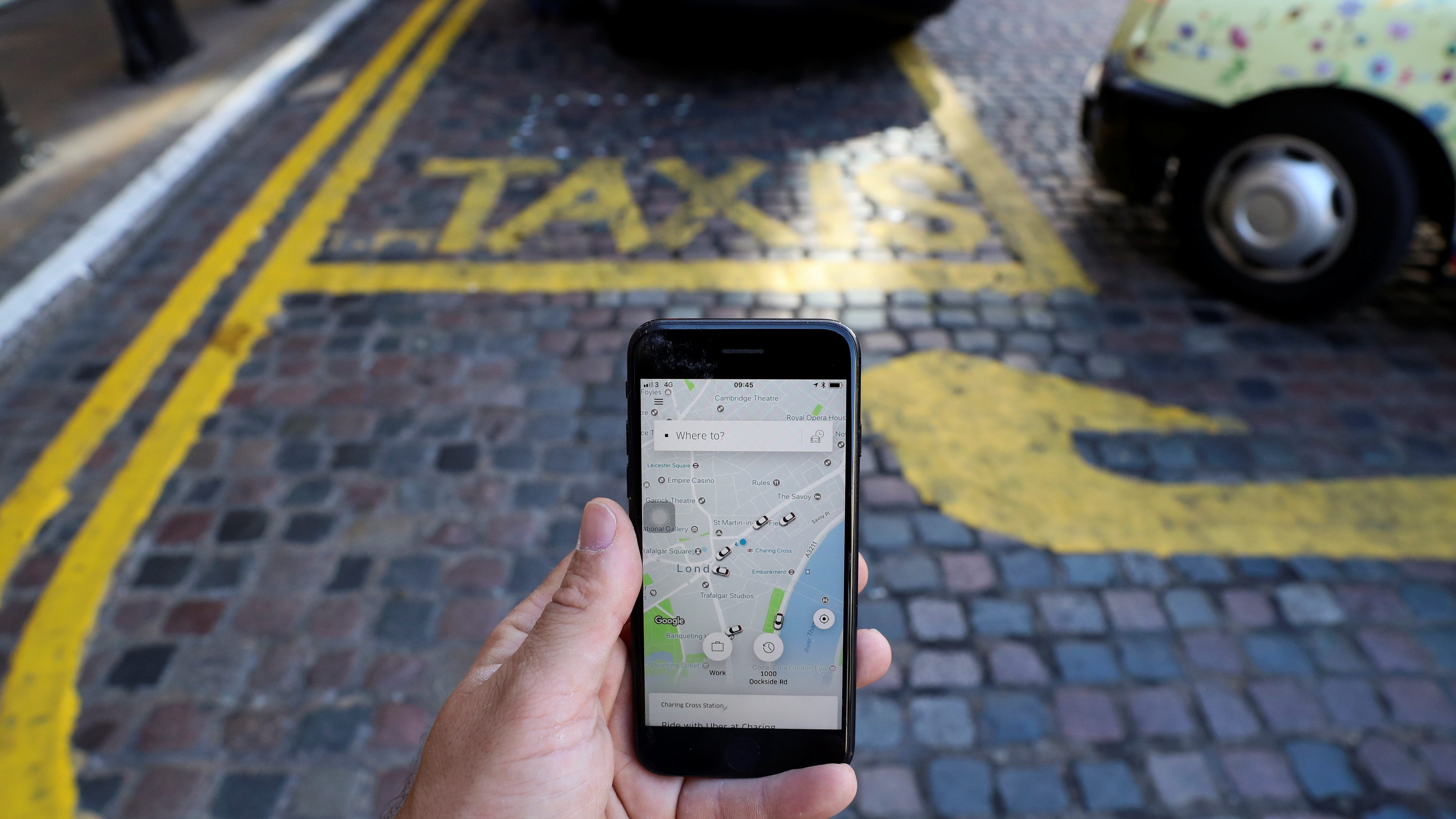 A photo illustration shows the Uber app and a black cab in London,