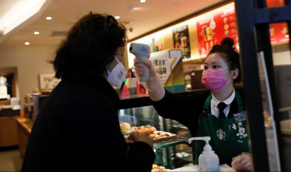 Worker uses a thermometer to check the temperature of a customer as she enters a Starbucks shop as the country is hit by an outbreak of the new coronavirus, in Beijing