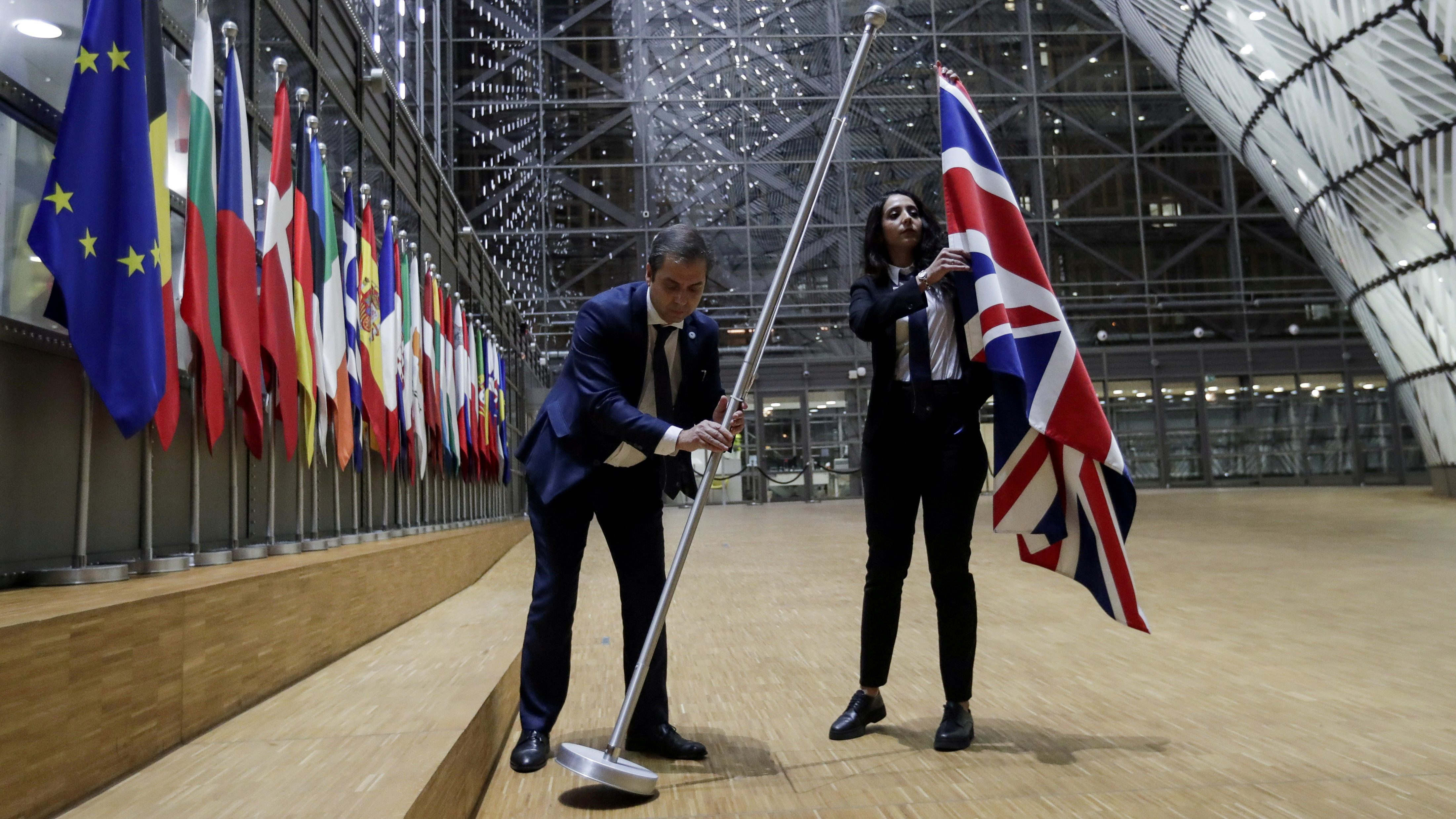 Officials remove the British flag at EU Council in Brussels