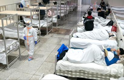Medical workers in protective suits attend to patients at the Wuhan International Conference and Exhibition Center, which has been converted into a makeshift hospital to receive patients with mild symptoms caused by the novel coronavirus, in Wuhan, Hubei province, China February 5, 2020. Picture taken February 5, 2020. China Daily via REUTERS ATTENTION EDITORS - THIS IMAGE WAS PROVIDED BY A THIRD PARTY. CHINA OUT. - RC2UUE9ADN51