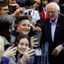 a photo of Bernie Sanders taking selfies with young people at a rally in New Hampshire