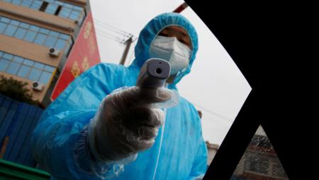 Photo of medical worker with temperature gun
