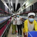 A masked woman rolls away carts of unused tools between rows of spinning machine at a factory owned by Hong Kong's Novetex Textiles Limited in Zhuhai City, Guangdong Province