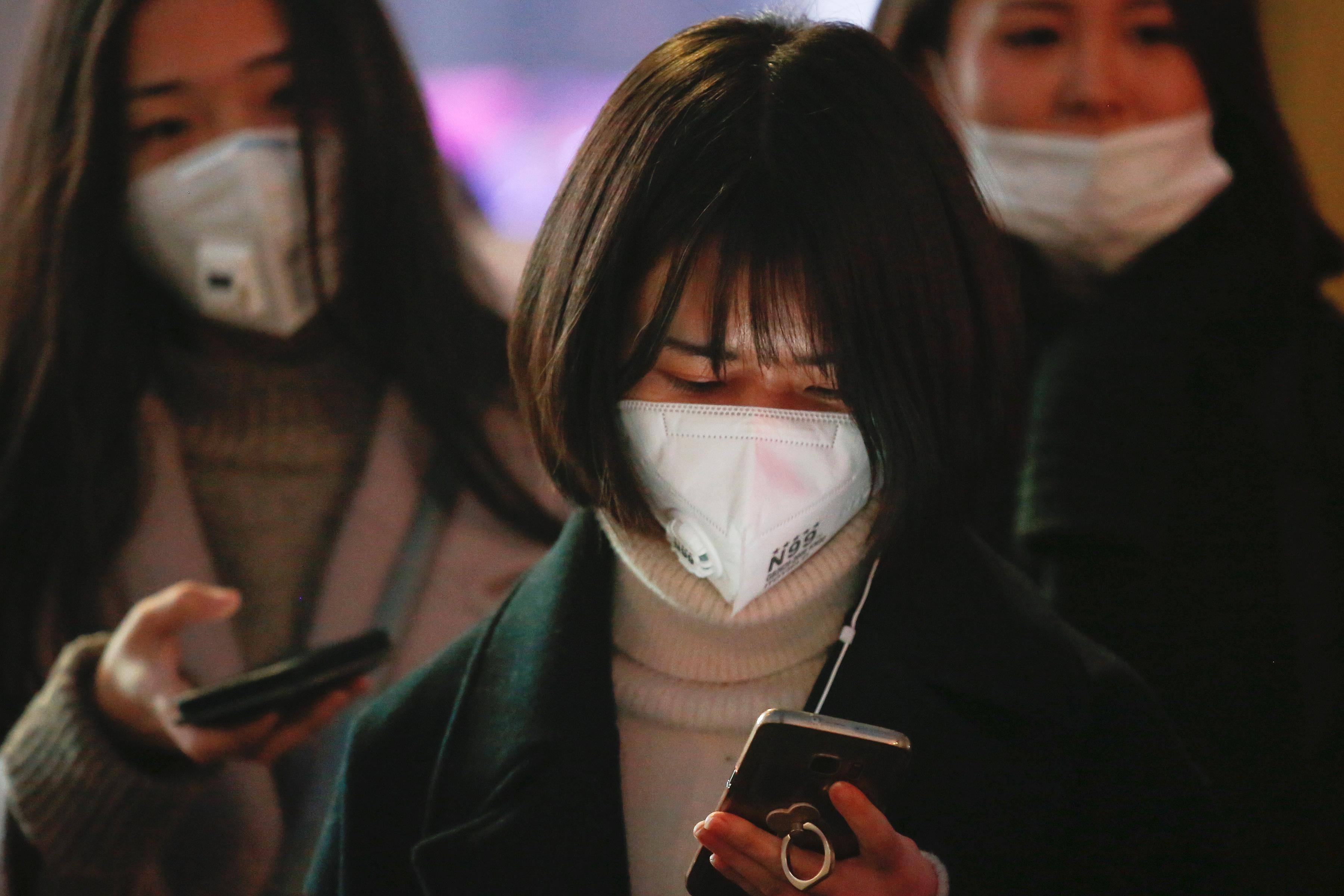 Women wearing face masks wait for the bu