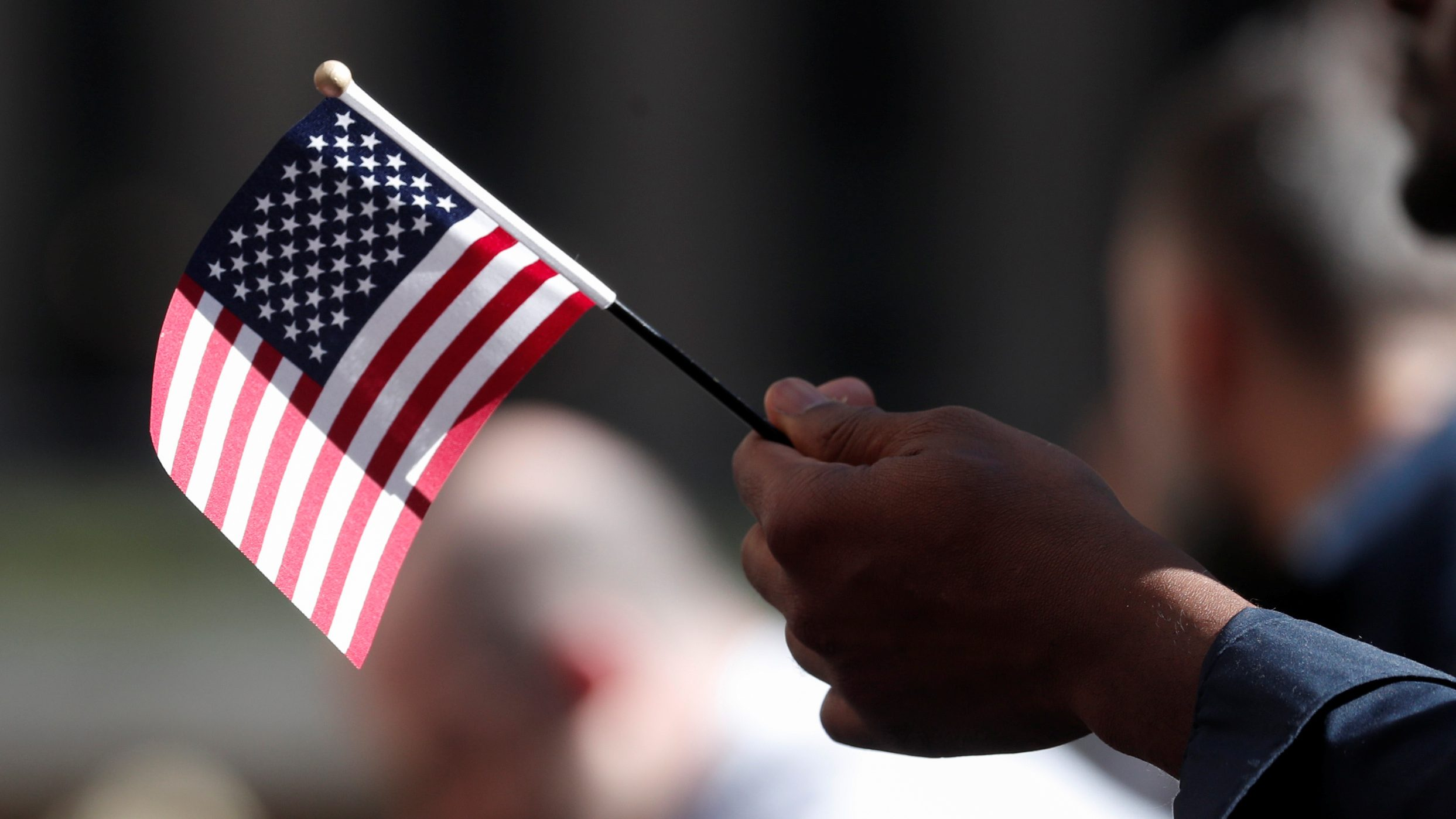 A citizenship candidate holds a flag during the U.S. Citizenship and Immigration Services (USCIS) naturalization ceremony at Rockefeller Plaza in New York City