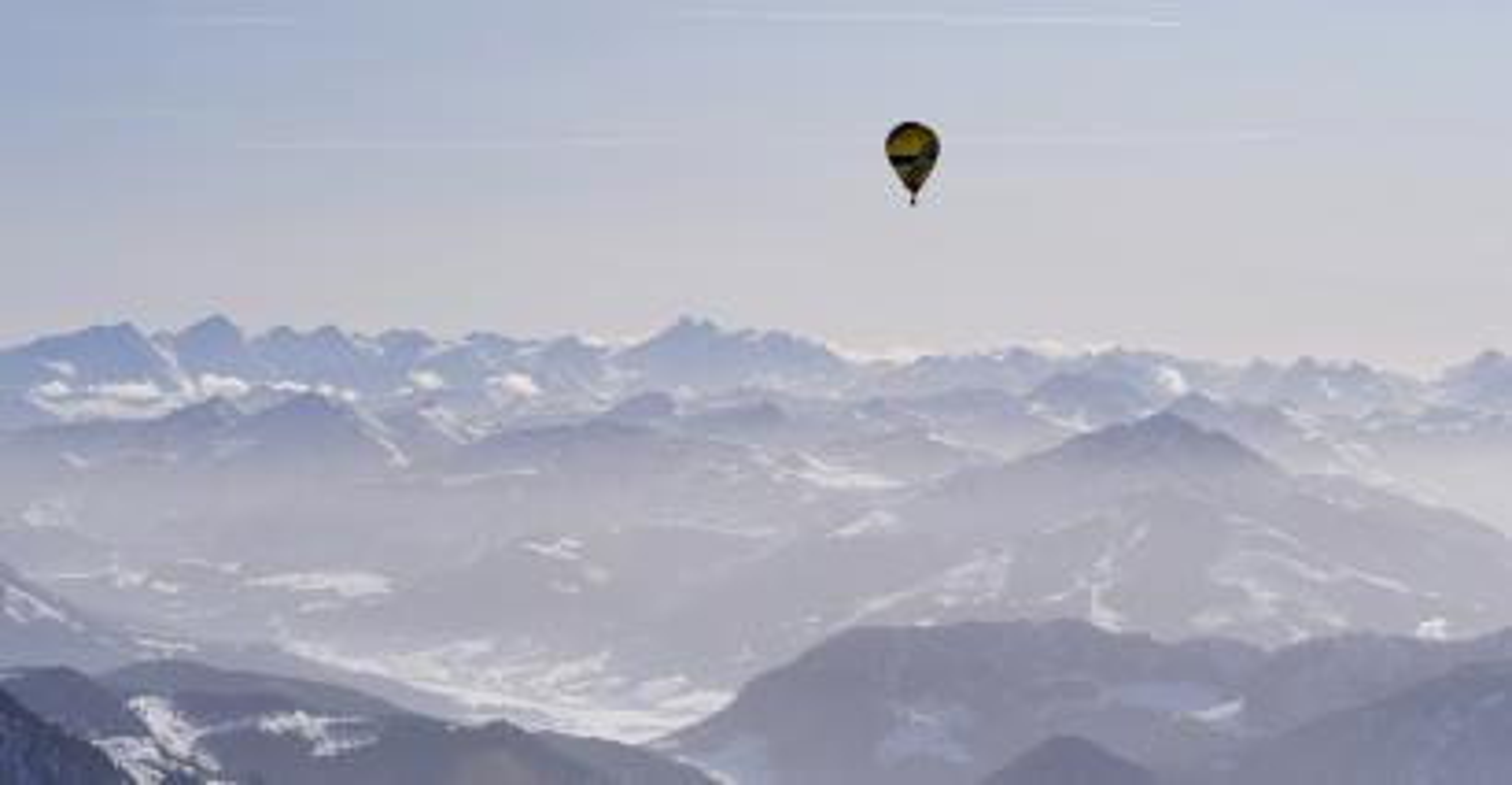Photo of a hot air balloon over mountaints.