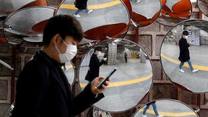 A man wearing a mask to prevent the coronavirus is reflected in the mirrors, in Seoul, South Korea, February 24, 2020.