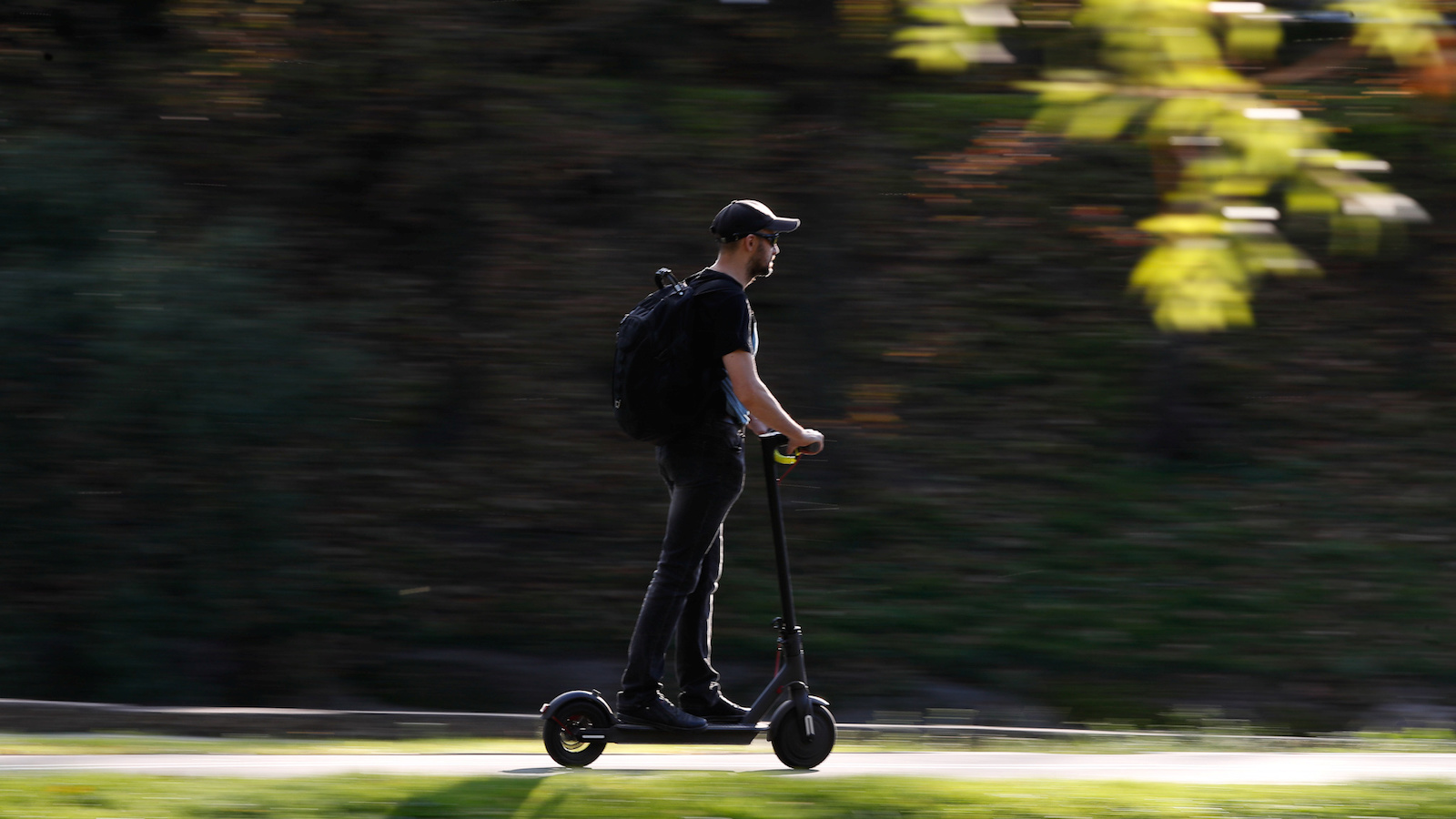 A man with a beard rides an electric scooter
