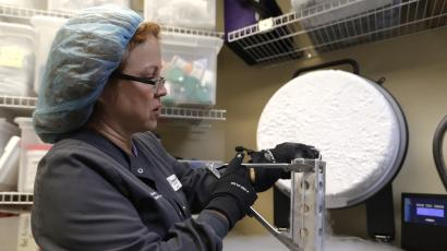 A person in a hairnet, sweatshirt, and gloves opens up a freezer of liquid nitrogen where human eggs are stored.