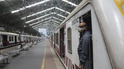 "A motor man wearing a mask looks on at a deserted train station in Mumbai, India, Sunday, March 22, 2020. India is Sunday observing a 14-hour ""people's curfew"" called by Prime Minister Narendra Modi in order to stem the rising coronavirus caseload in the country of 1.3 billion. For most people, the new coronavirus causes only mild or moderate symptoms. For some it can cause more severe illness. (AP Photo/Rafiq Maqbool)"