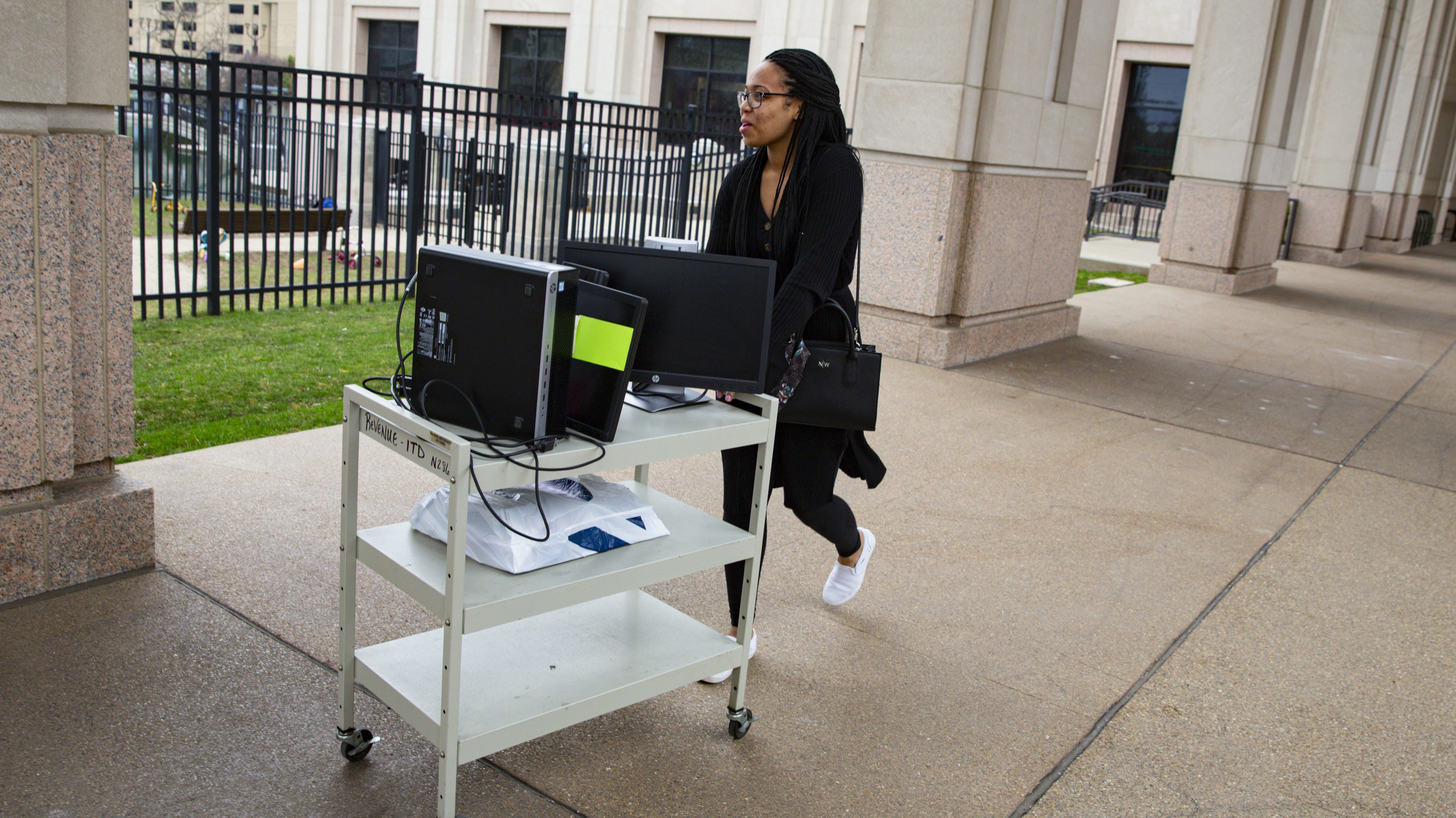 An employee at the Indiana Department of Revenue moves her computer equipment from her office on March 24 to allow her to work from home.