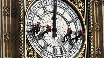 FILE- In this file photo dated Monday, Aug. 18, 2014, workers abseil outside the clock face as they clean Big Ben's clock tower of the Houses of Parliament in London. According to reports published Sunday Oct. 18, 2015, the chimes of Big Ben may fall silent for many months as urgent repairs are carried out to the clock and the tower, which must begin as soon as possible.